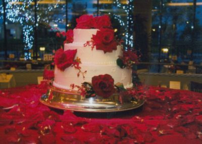 Fresh Flowers on a Beautiful Wedding Cake sitting on a bed of Red Rose Petals